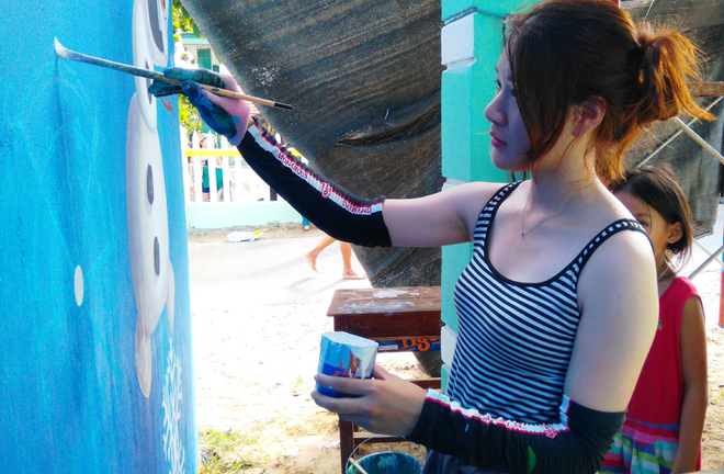 A Korean painter colouring the wall of a house in the village (Photo: VNS)